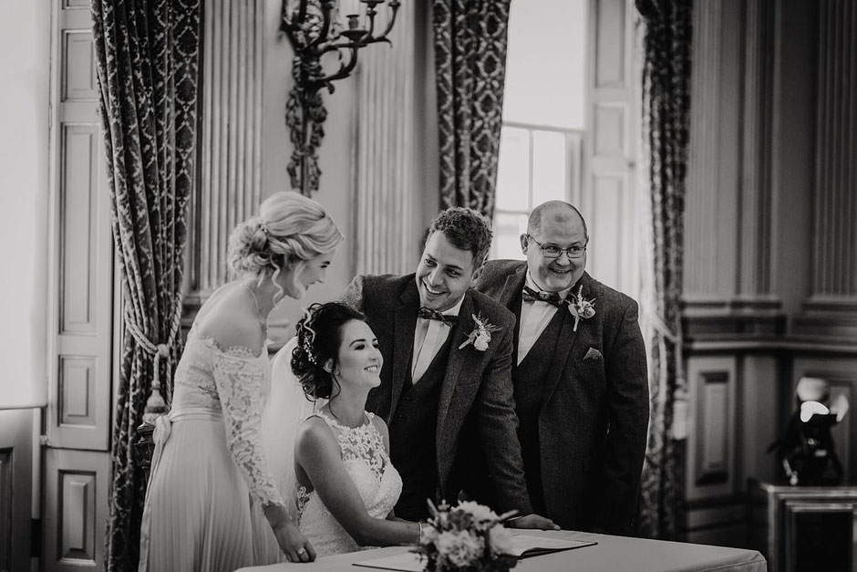 natural black and white photograph of a bride and groom signing the register