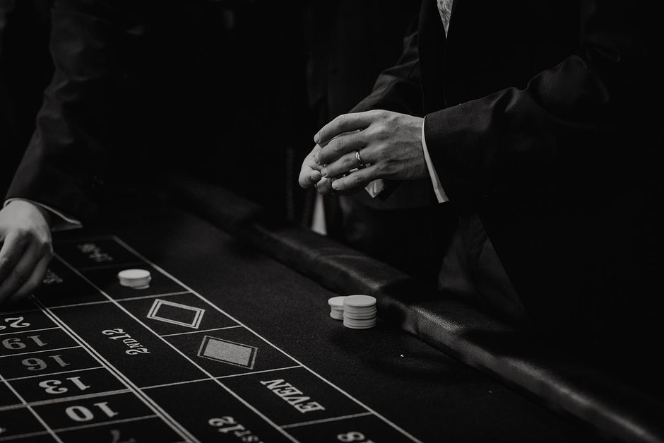 black and white photograph of a grooms hand as he plays poker