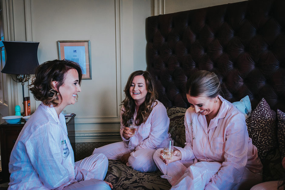 bridal party sat on a bed laughing with glasses of champagne all dressed in matching pyjamas