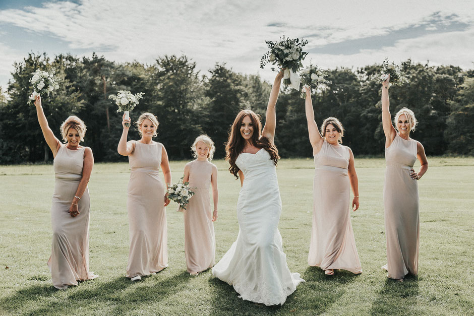 a bride and her bridesmaids walking toward the camera all holding their bouquets up in the air