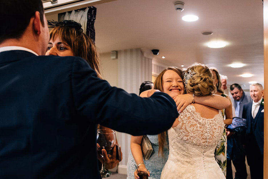 a bride being hugged by one of her guests