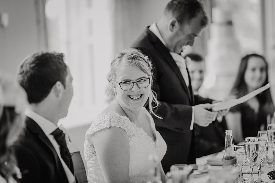 black and white image of a bride laughing towards the groom during speeches