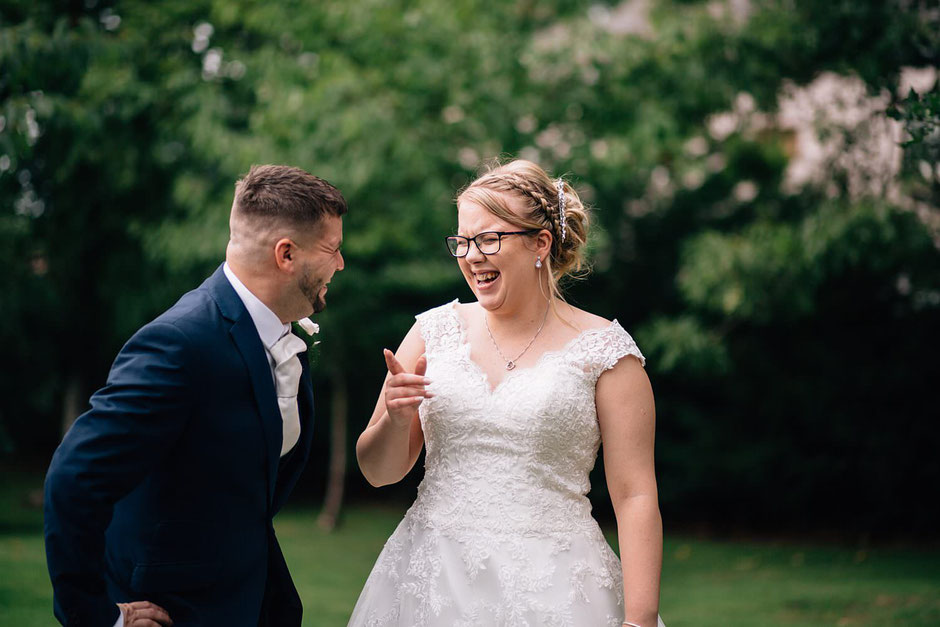 candid photograph of a bride and her bridesman laughing