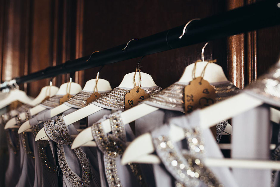 Close up photograph of grey embellished bridesmaids dressed on white hangers with brown name tags