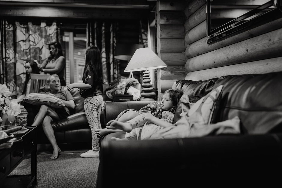 a black and white photograph of some children sat on a couch staring at a tv inside a log cabin