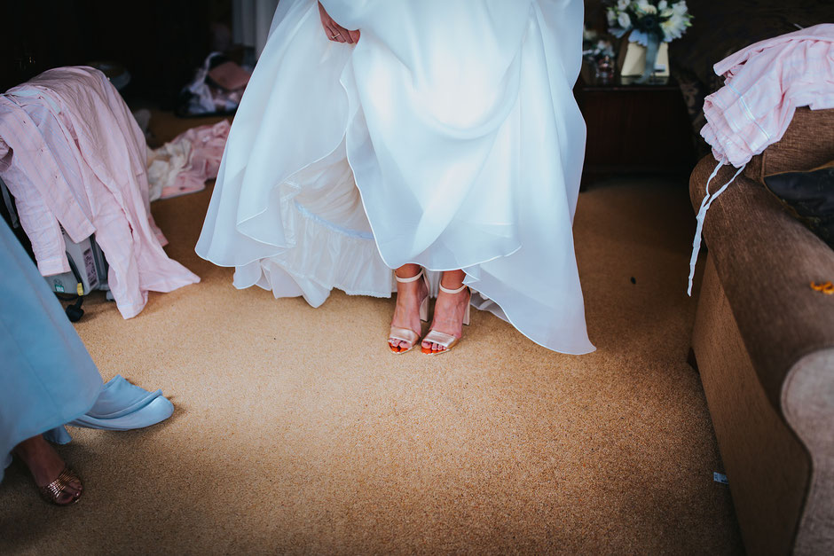 a bride holding up her dress so you can see her gold shoes underneath