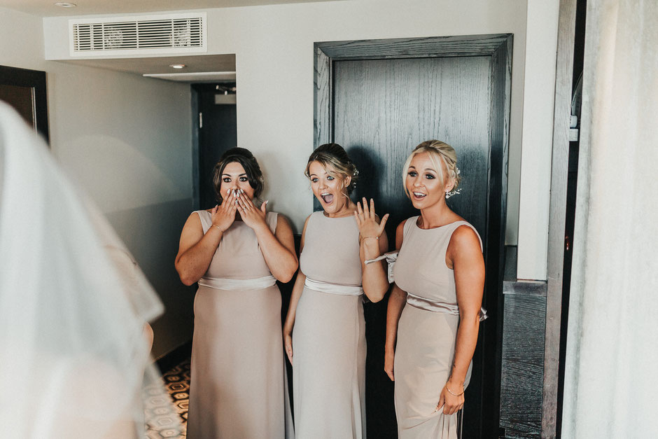 three bridesmaids with happy and shocked faces when seeing the bride in her dress for the first time