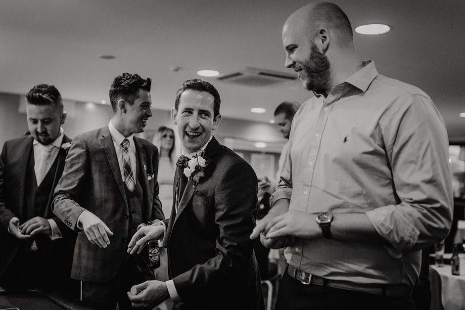 black and white portrait of a groom laughing with friends whilst playing poker