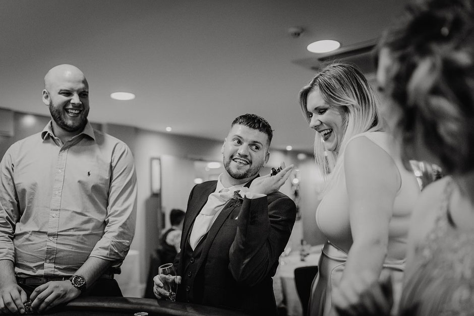 black and white photograph of a wedding guest looking happy with his winnings from poker