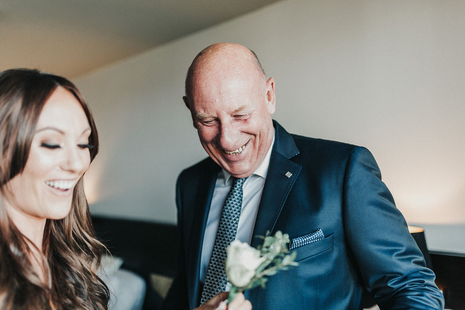 a bride helping her father attach his button hole to his suit