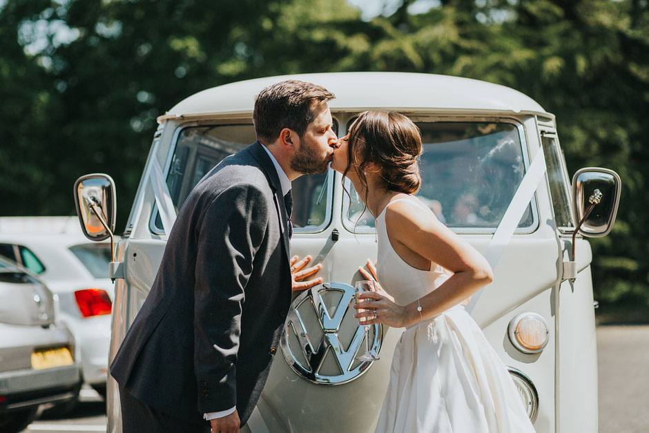 bride and groom kissing infant of their vw camper van