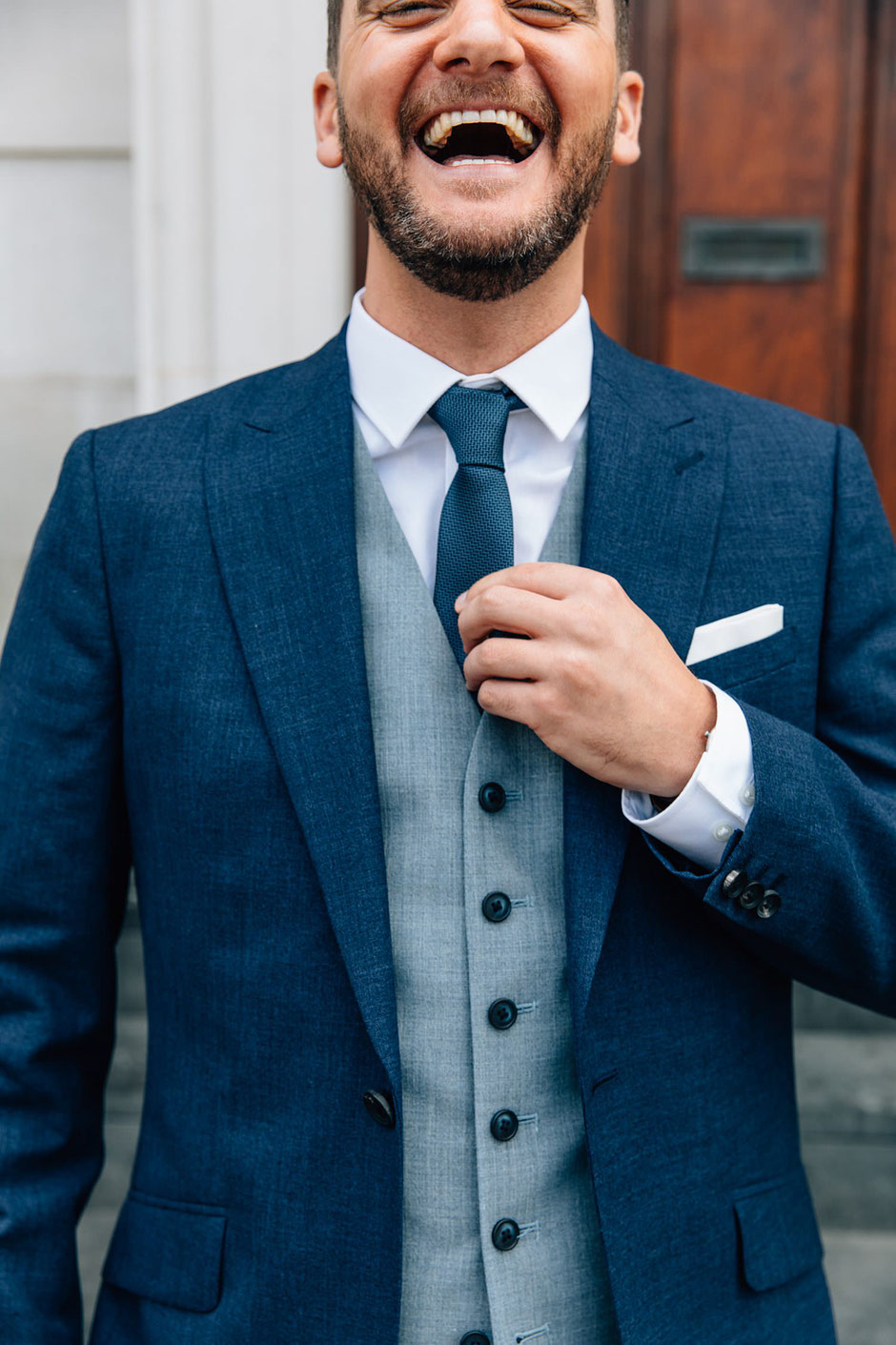 a portrait of a groom dressed in a blue and grey suit laughing whilst touching his tie