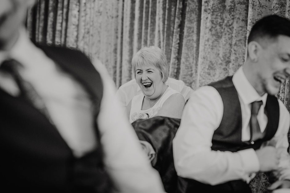 candid black and white photograph of a lady laughing during wedding speeches