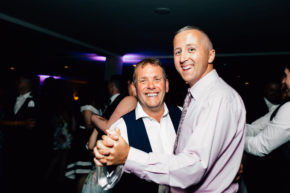 two men dancing during a wedding reception at ribby hall