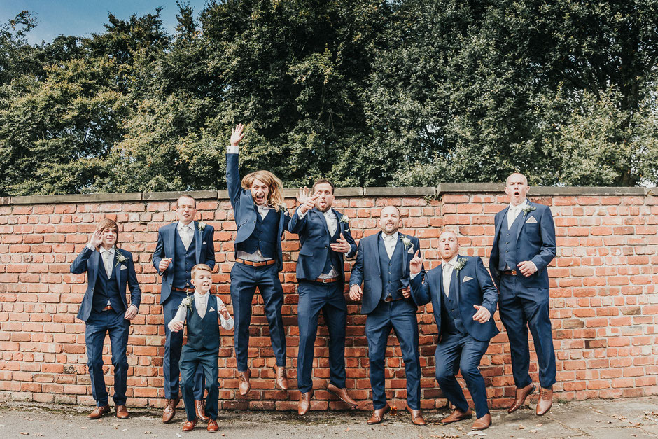 fun portrait of the grooms party all jumping in the air in blue suits and brown shoes
