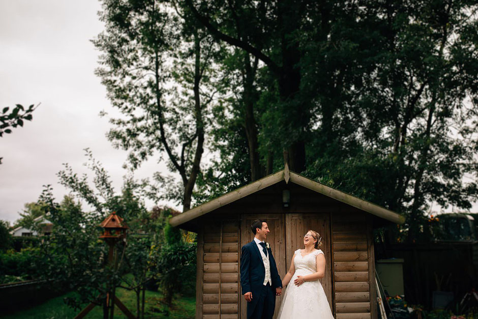 bride and groom laughing whilst stood infant of a wooden shed