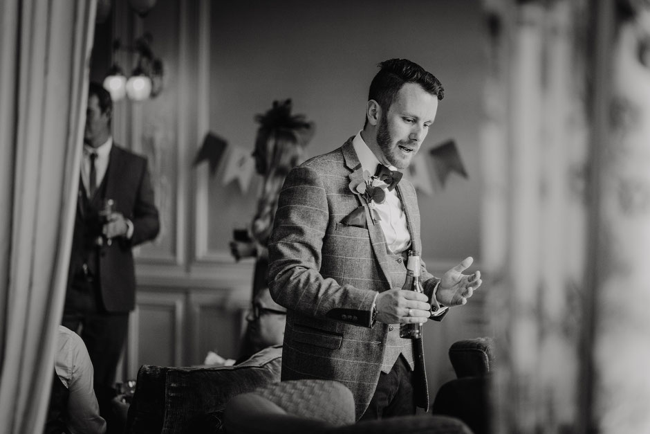 candid black and white photograph of a groom chatting to guests at his wedding reception