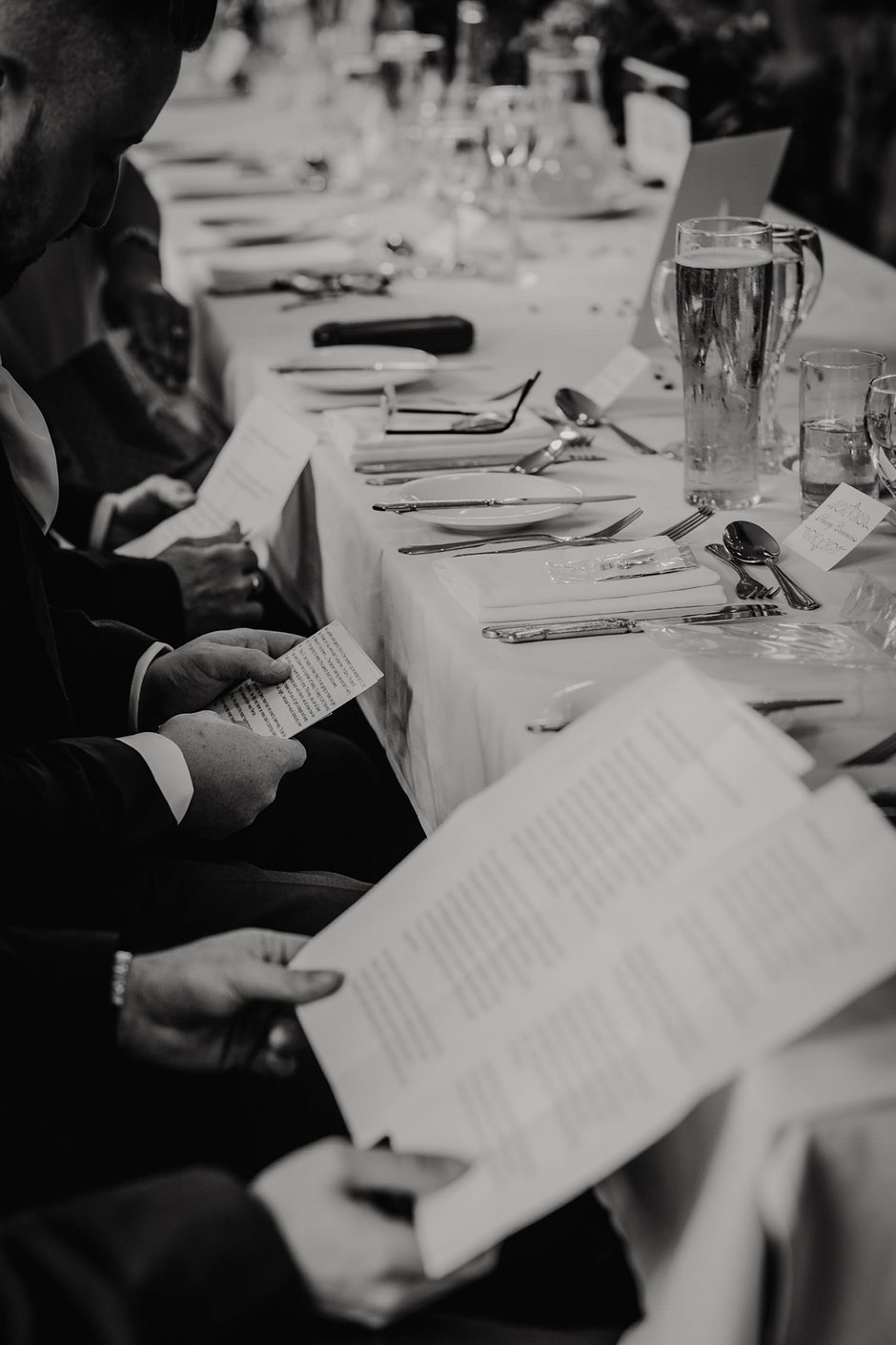 black and white photograph of three men holding speeches during a wedding breakfast