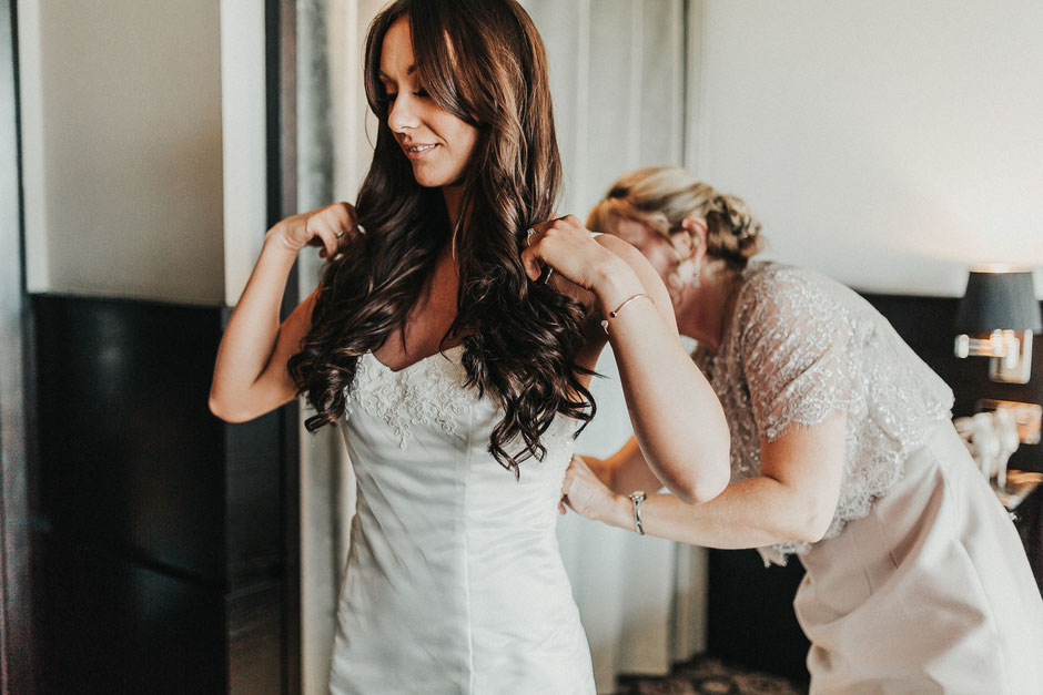 a bride in a hotel room being helped into her bespoke dress by her mum