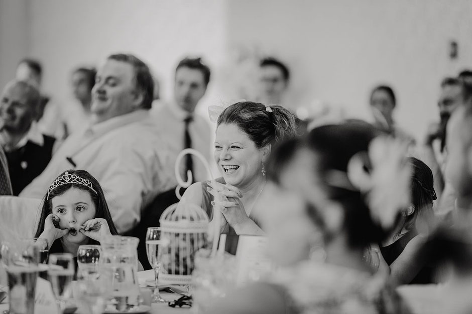 black and white photograph of a wedding guest laughing during speeches