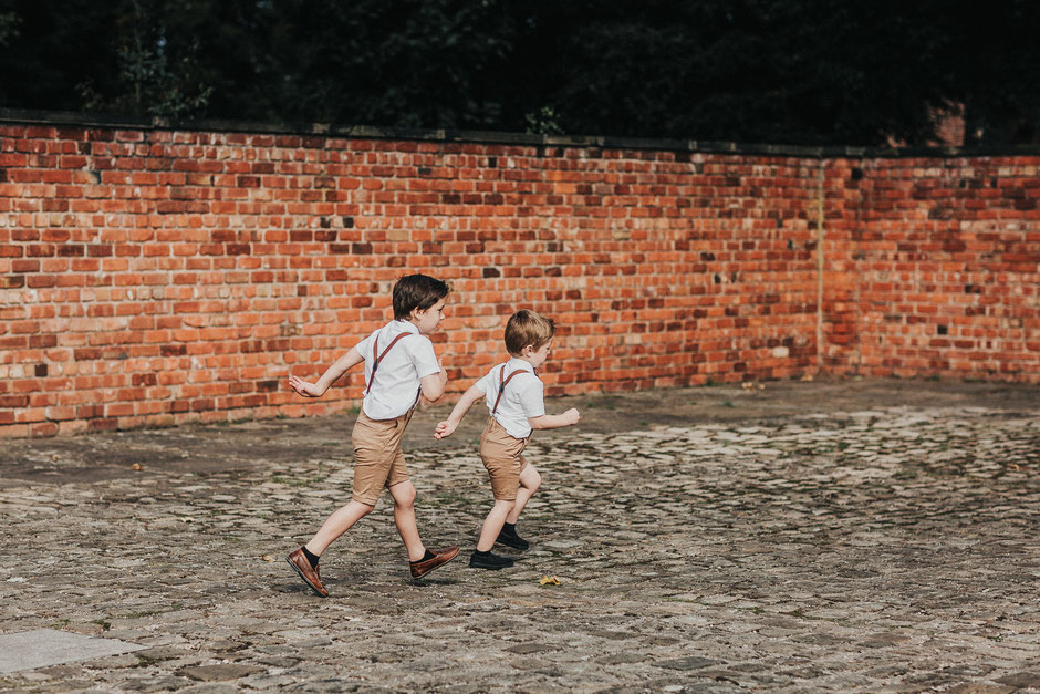 two little boys running around in the courtyard of meols hall
