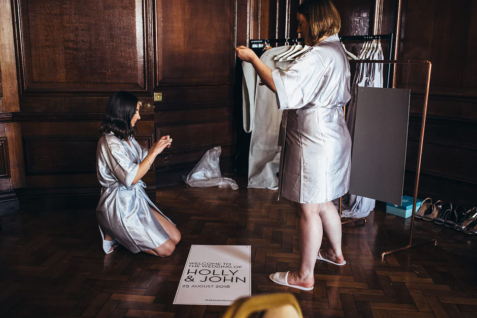 two bridesmaids dressed in silk robes hanging a wedding sign