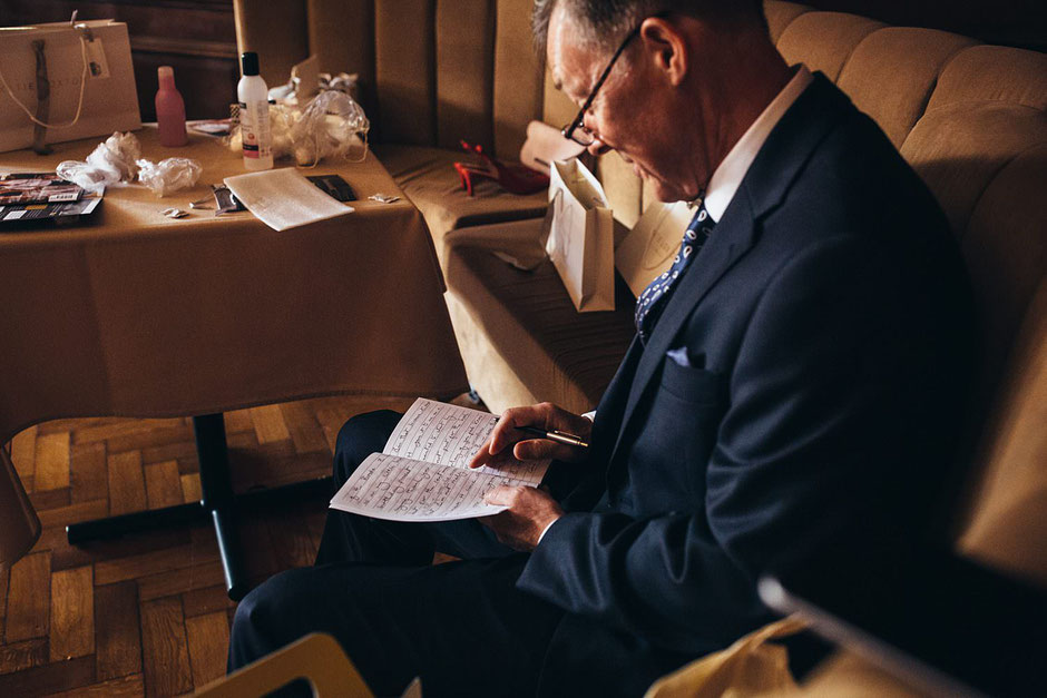 a man sat down looking in a notebook where he is making final notes for his father of the bride speech