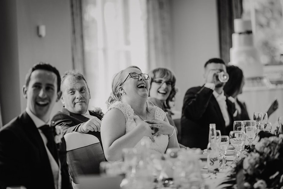 black and white photograph of a bride laughing during speeches
