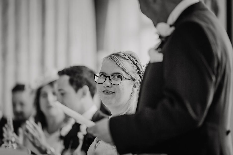black and white photograph of a bride looking up at her dad during his speech