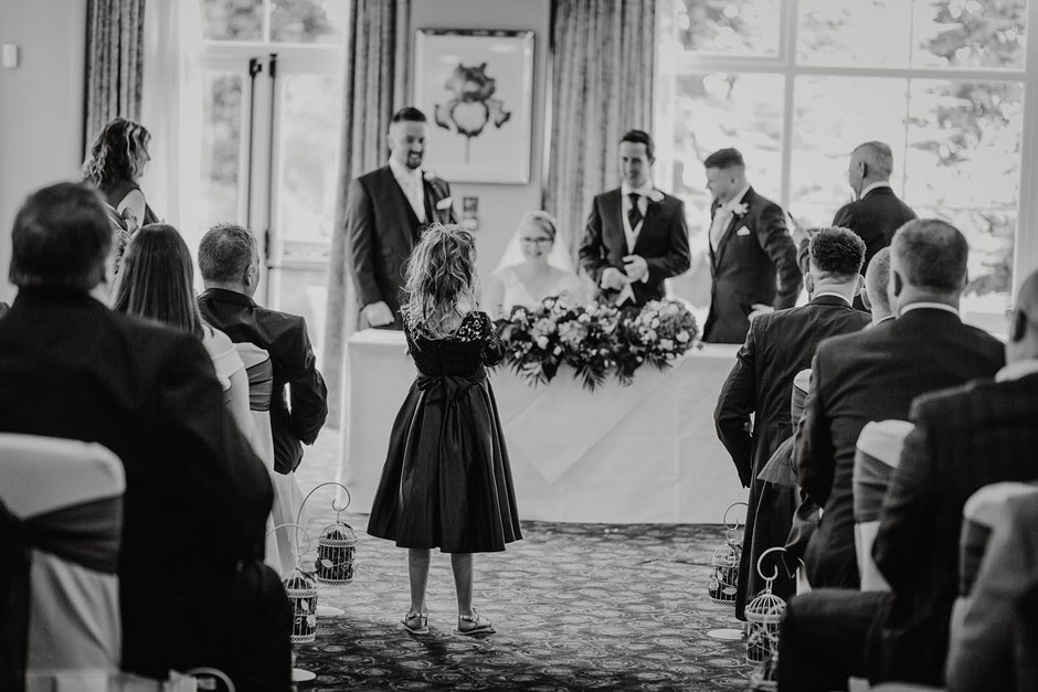 black and white photograph of a little girl taking a photo at a wedding