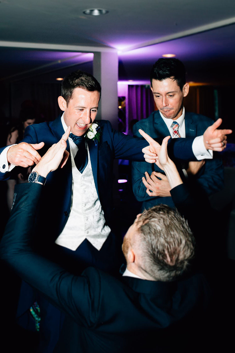 a groom and his friend laughing with each other on the dancefloor