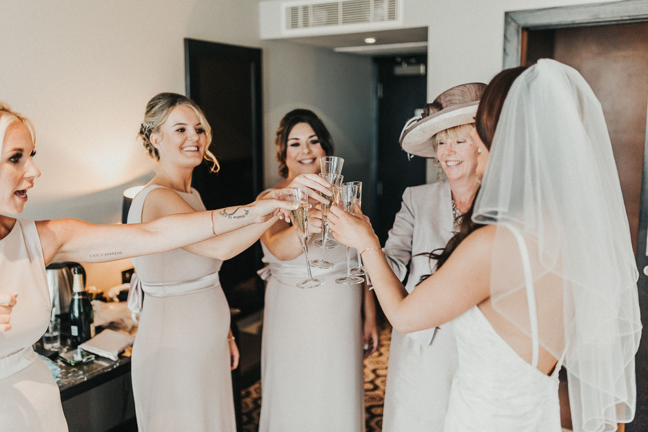 a bride, her mum and bridesmaids all toasting
