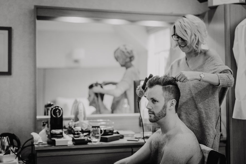 Black and white photo of a groom having his hair styled on the morning of his wedding day