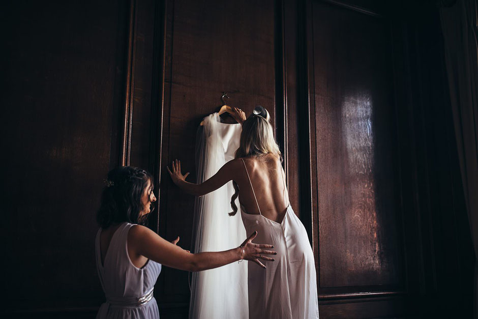 two ladies, one stood on a chair reaching for a wedding dress that is hung on a wall
