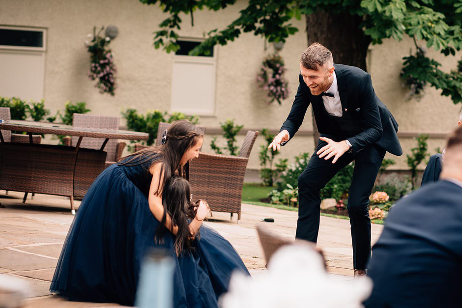 a photograph of a man chasing two bridesmaids at a wedding