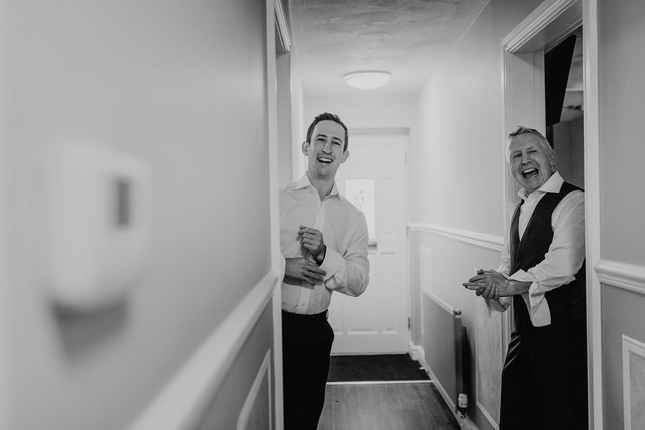 A black and white photograph of a groom and his dad in a corridor laughing