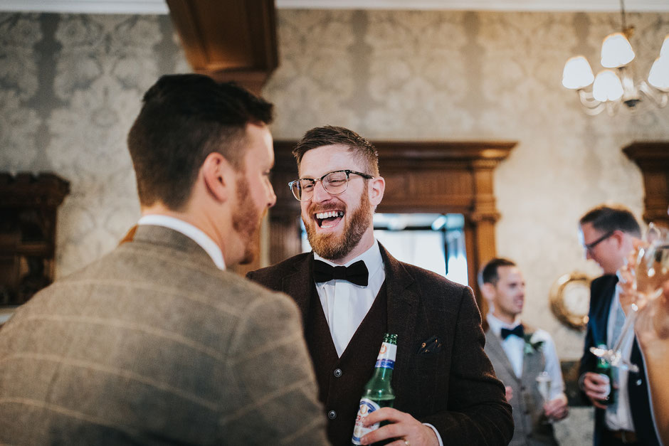 candid photo of a wedding guests wearing glassed and a bow tie laughing towards the groom