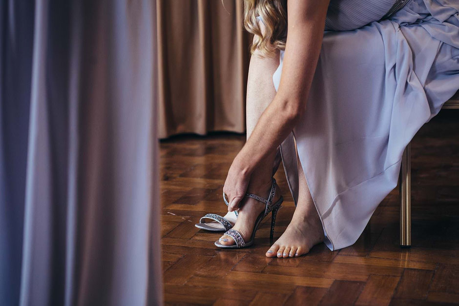 a close up of a lady putting her shoes one