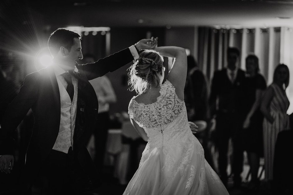 black and white photo of a groom spinning his bride