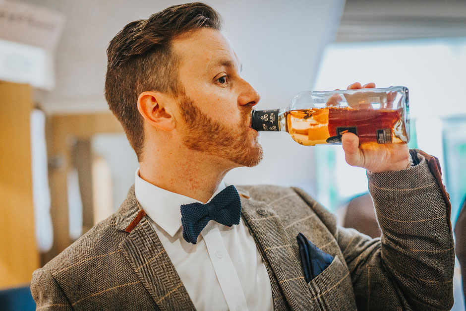 Groom dressed in a tweed suit with bowtie drinking straight from a bottle of whiskey