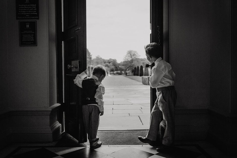 black and white photograph of two boys holding open a large set of doors