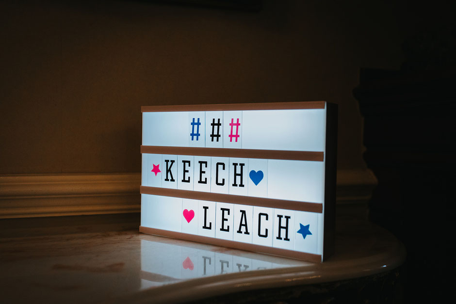 a light up sign with the wedding hashtag displayed in colourful lettering