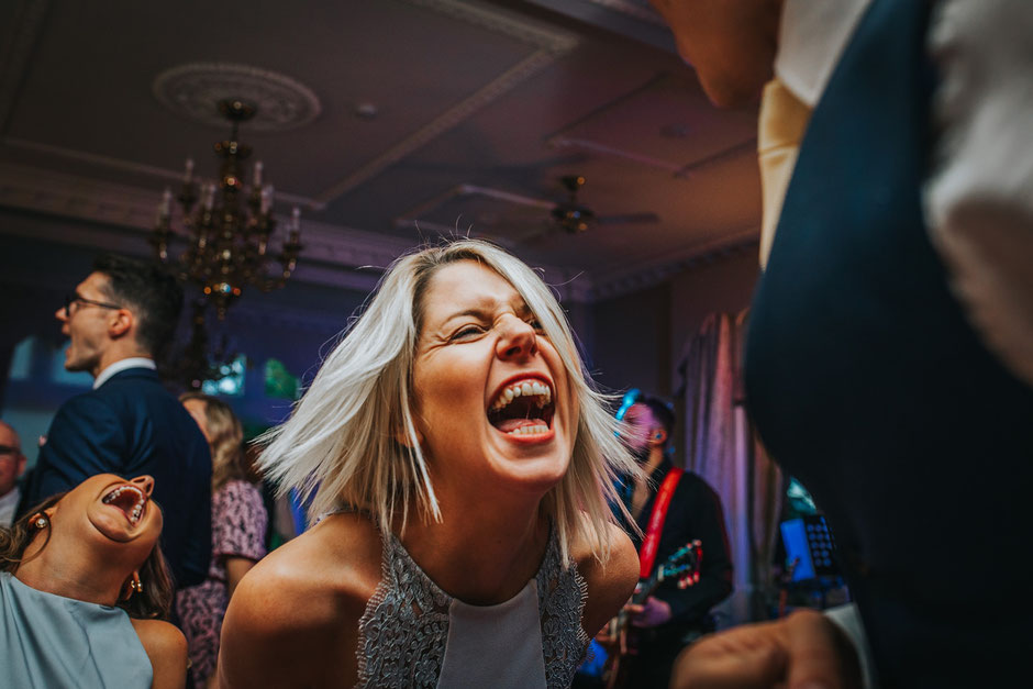 two women laughing at a wedding reception