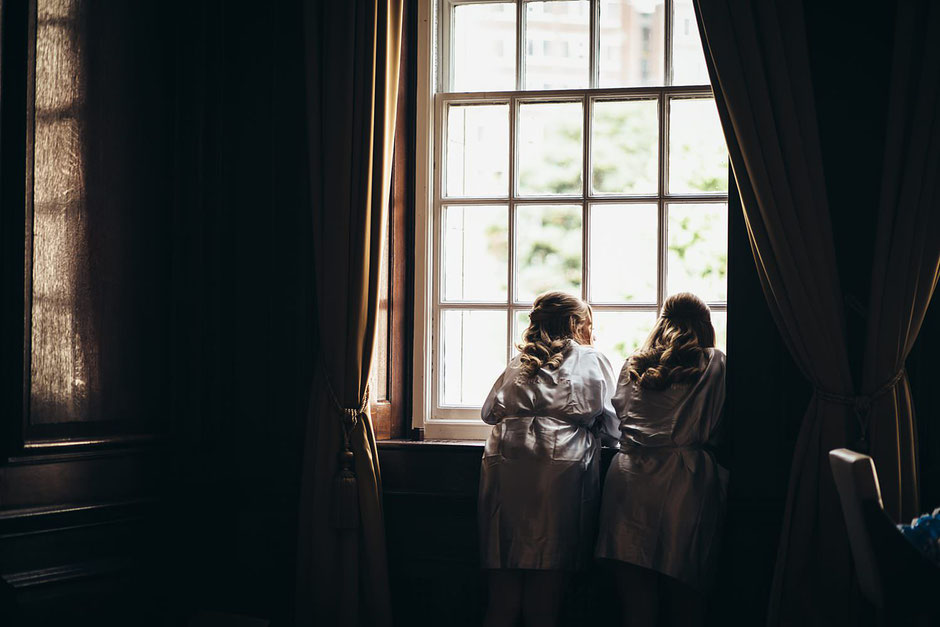 two bridesmaids dressed in silk dressing gowns looking out of a tall window