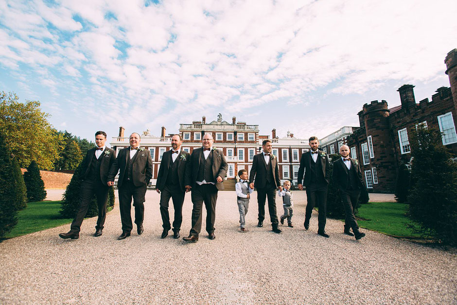 Grooms party in tweed suits walking down the driveway in front of Knowsley hall