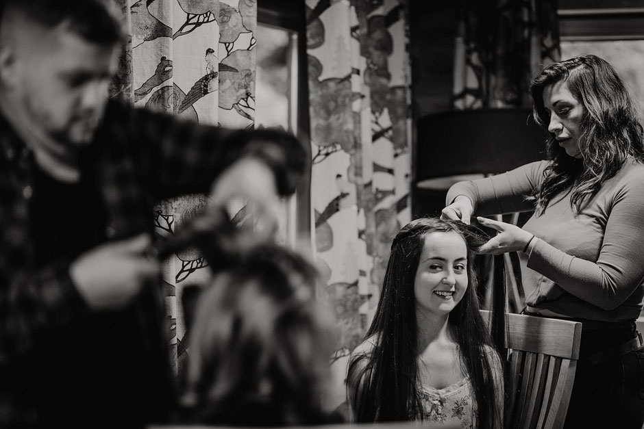 black and white photograph of two bridesmaids smiling at each other having their hair done