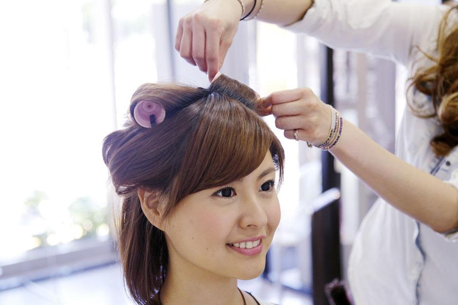 髪にロッドを巻く女性
