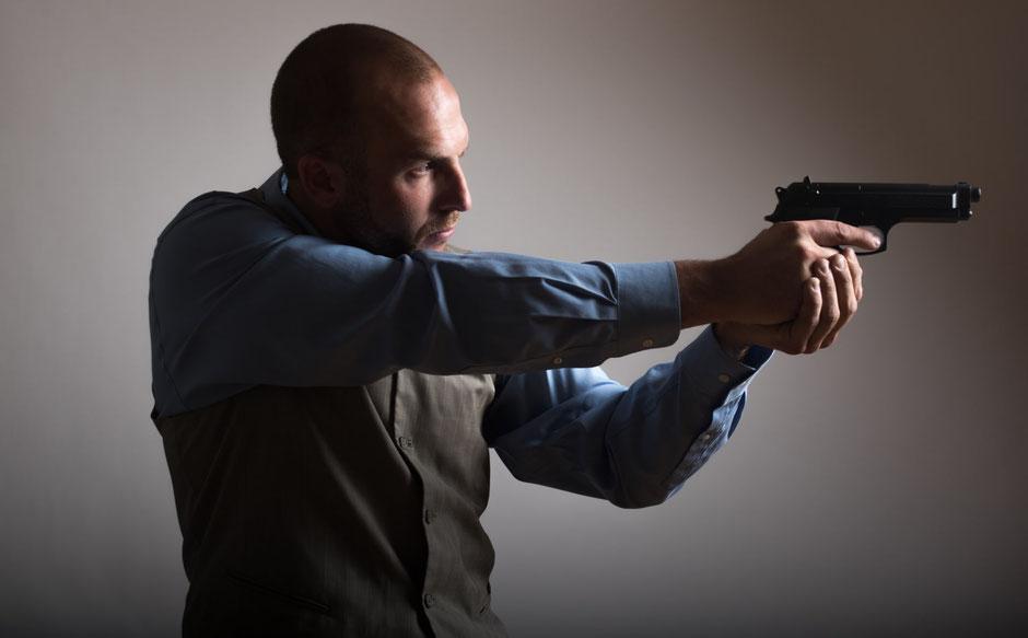 銃で狙いを定める男性