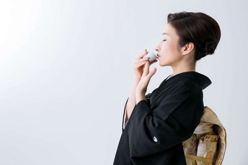 日本酒を飲む和服の女性