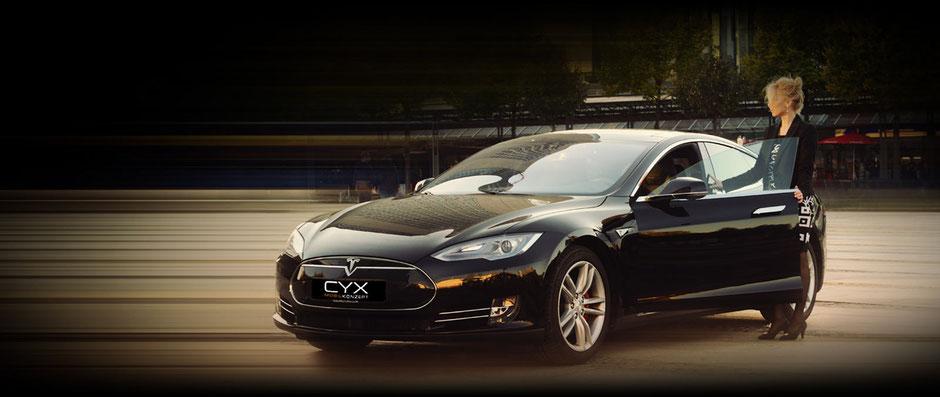 Blonde Frau mit hochgesteckten Haaren im Business-Outfit, die gerade in einen schwarzen Tesla einsteigt, der Hintergrund ist verschwommen.